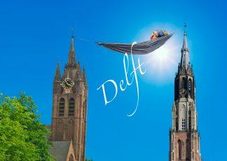 ansichtkaart Delft met oude en nieuwe kerk en het meisje met de parel in een hangmat ertussen